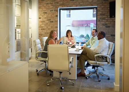 happy customers and staff sitting around a conference table in the somerville showroom